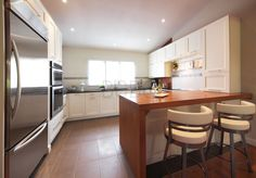 Contemporary kitchen style with maple cabinet painted in white lacquer.