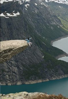 Sentando-se na beirada da rocha Trollunga, na Noruega.