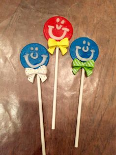 """After rolling the airheads our with a rolling pin, use circle-shaped metal cookie cutters to create the infamous Airhead Smiley Face balloon of your color choice.  Cut strips from the Mystery Color Airhead to form the face.  And with icing as """"glue"""", attach the lollipop stick and adorn with edible bow or anything else!"""