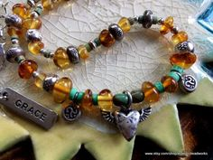 Stunning One of kind Southwestern Bohemian style necklace made with genuine Baltic Amber, Turquoise, and Hill Tribe Silver. A flying heart silver charm adorns the center of the necklace really making a statement. The two tiny Karen Hill Tribe OM Charms are perfectly placed. There is also a removable GRACE charm that I love! The moon and star beads add a bit of whimsy. I also love the Baltic Amber from Poland. It is said to have anti-inflammatory properties. The feel of it is like nothing…