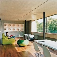 Built for a young family of Spartan-minded clients, architect Felix Oesch's spare, concrete prefab outside of Zurich is a marvel of clean living.Meili and Anais lounge on a Transform sofa by Moroso. Photo by Hertha Hurnaus.  Photo by: Hertha Hurnaus