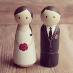 A custom hand painted set of toppers. The bride is wearing a white dress and is holding a red rose bouquet. The groom is wearing a black suit and red rose buttonhole. Custom toppers are available at www.eefaa.etsy.com