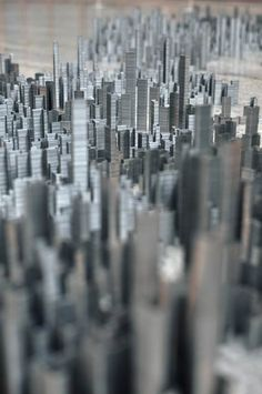 Artist Peter Root has been busy collecting staples and turning the boring metal office supplies used for bundling paperwork into mesmerizing city scapes. Using 100,000 staples to cover an approximate area of 600cm x 300cm (118 inches x 236 inches), Root's work of art entitled Ephemicropolis was born. Root broke down the stacks of staples into varying sizes, the tallest of which measures 12cm high (5 inches) and the smallest which consists of a single staple.