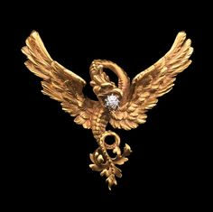 A French carved 18ct yellow gold chimera brooch, the chimera in flight with hand-chased feathers and a claw-set old brilliant-cut diamond weighing an estimated 0.20ct in its beak, the tail of curved, foliate Art Nouveau design.