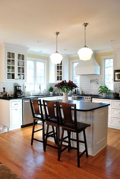 Black granite countertops with white cabinets and white subway tile backsplash