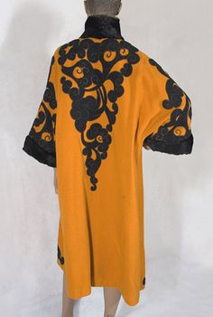 Orientalism-inspired wool coat (back view) c.1912. The arrival of the Ballets Russes in Paris in 1909 detonated an aesthetic bombshell in the West. Decors for the ballet by Russian painter Leon Bakst used exotic patterns, brilliant colors, and lush fabrics. The new trend in all the graphic arts was termed Orientalism. With its striking palette of orange, green and black, this brilliant coat perfectly captures the mood of the period.