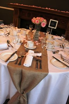 Burlap table runners, shown here with soft pink roses and napkins tied with pink ribbon and lace. At Barony Castle.