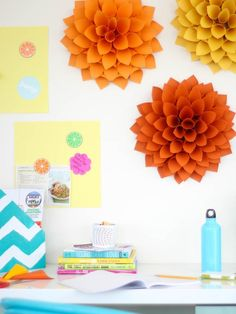 Video tutorial on how to make these giant paper dahlias. You just need 60 4-in square pieces of paper, a cut circle base, and double stick tape.