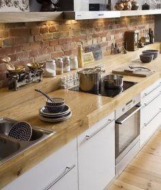 "Rustikal und so gemütlich:""Wooden counter top, white kitchen cabinets and brick wall."""