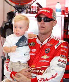 Kevin Harvick, driver of the #4 Budweiser Chevrolet, holds son Keelan in the garage area during practice for the NASCAR Sprint Cup Series Quaker State 400 presented by Advance Auto Parts at Kentucky Speedway on June 27, 2014 in Sparta, Kentucky.