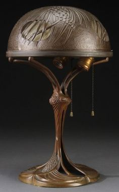 ART NOUVEAU BRONZE TABLE LAMP, Georges Leleu (French 1883-1961). The pierced shade with embossed pine cone design containing four frosted glass panels, raised on a stylized pine cone and needle bronze base. Inscribed on foot rim G. Leleu. Height 16.5 inches (42 cm).