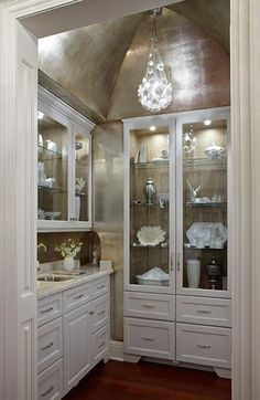 White cabinetry with glass doors. Silverleaf thing on the ceiling