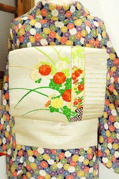 四季の草花で彩られた屏風のような装飾から楚々とのぞくように咲く菊花が凛と美しく織り出された名古屋帯です。