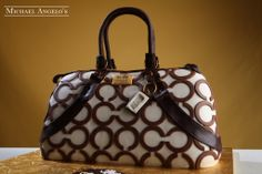 """White Coach Shoulder Purse #25Handbag  This designer purse cake features Coach's famous double """"C"""" monogram atop smooth white fondant. The chocolate brown handles and strap bring this cake to life. The Coach tag is also included as a nice finishing touch."""