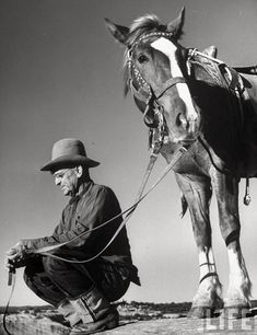 Utah, 1947– Man sitting holding his horse's reins  –Loomis Dean
