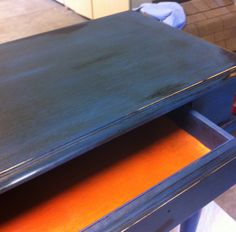 This started as a black lacquered side table. It was painted with Annie Sloan Napoleon Blue on the outside and Barcelona Orange on the inside. The table was waxed with light wax and then dark wax. The drawer was waxed with dark wax only.