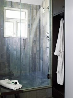 For a distinguishable look, combine different types of tile on shower walls and floors. This shower became a masterpiece with porcelain tiles of varying sizes covering the walls. Blue mosaic glass tiles line the shower floor and also appear as accents on the wall.