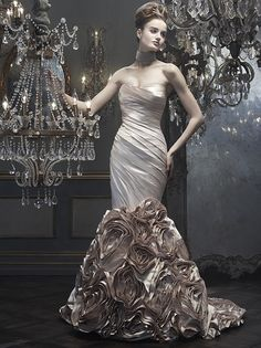 Gown style B074 has a fitted elongated bodice of ruched silk satin and is accented by a flared skirt formed by ribbons of luxe italian duchess silk that create elegant rosettes. Available in platinum blush and ivory.