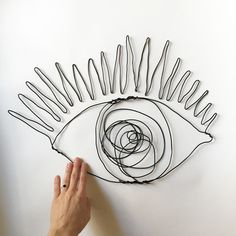 """The Wire Bright Eye is hand made by me (hi I'm Kate!) using black aluminum wire. Each one is 19"""" wide X 12.5 high,custom made, and ready to hang. All art is shipped in a sturdy cardboard box for protection. These sculptures come with a title and signature card. For custom wire dra"""
