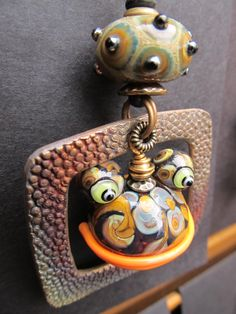 Glass frog bead with bronze frame  pendant by Wayne Robbins and Judie Mountain. www.mountainrobbins.com