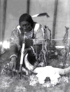 Dakota man with calumet kneeling by altar inside a tipi. Photographed by Edward S. Curtis, ca. 1907.