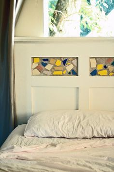 Homemade headboard by moretrees, via Flickr.  I love the white, the wood panels, but not the tile pieces.  Now stained glass, that would be cool!