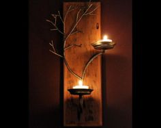 This pair of tree wall sconces are welded up from mild steel hammered to its final form and then given clear satin protective coating. When illuminated with tea light or votive candles the candlelight creates soft reflections on the tree branches and interesting shadows on the wall behind it. Set includes one left hand and one right hand sconce. Each sconce holds two votive or tea light candles.Color is a silvery gray with some darker gray highlights.  These sconces will and a warm glow to…