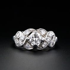 This is a wonderful vintage ring from the 1950's. This 14 karat white gold diamond engagement ring features a .55 carat round brilliant cut diamond highlighted by swirls of diamonds. A great stand alone ring!