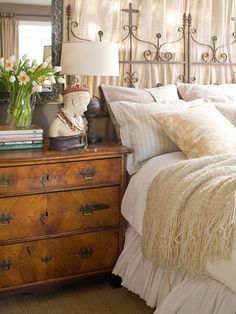 Create layered luxury and highlight textures in a bedroom in three easy steps. Start with a clean, white backdrop: a white coverlet or quilt and bed skirt. Stack your pillows, starting with a khaki sham, then a simple stripe and an oversize floral with a colored background. An extra blanket provides the finishing touch.