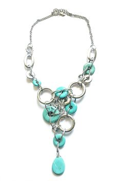 There are statement necklaces and then there are statement necklaces. This turquoise and silver necklace truly makes a statement. Multiple silver tone circular disks in various design and sizes combined with turquoise colored stones with a adjustable chain. These piece is large but not heavy measuring 24 inches long adjustable up to 26 inches. The necklace has an 8 inch drop.  Turquoise Cascade Necklace by Ottoman Imports. Accessories - Jewelry - Necklaces Kentucky