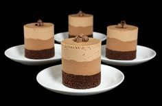 A photo of 4 Chocolate Mousse Cakes layered with Dark Chocolate Cake, Bittersweet Chocolate Mousse and Milk Chocolate Mousse displayed on small white dessert dishes with dessert forks with a black background. Mini Desserts, Chocolate Desserts, Just Desserts, Delicious Desserts, Yummy Food, Chocolate Cake, Chocolate Moose, Chocolate Pavlova, Gourmet Desserts