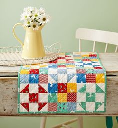 Sew a bright table topper using precut print strips and solid white. The white makes the colors pop.