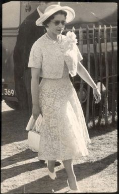 Arriving at a Windsor cocktail party, in 1959, wearing a lemon two-piece, wide-rimmed hat and sunglasses, Queen Elizabeth prepared to celebrate her horse 'Above Suspicion''s earlier triumph at Ascot.