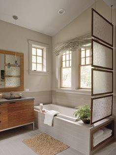 Ample tilework in varying shades of gray and brown creates a relaxed, peaceful atmosphere. Found on the floors, along the walls as wainscot, and as the tub surround, this material unifies the area. Small, tightly spaced half-round tiles enhance the shower area. (Photo: )