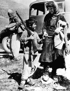 An Albanian boy carries a rifle as he flees to Yugoslavia with his mother after the Italian invasion of Albania, 1939
