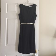 Calving Klein never worn black dress Gorgeous black dress.  Simple and classic with a cream colored belt.  Zip up back and gold latch at neck.  Pictures don't do it justice. Calvin Klein Dresses
