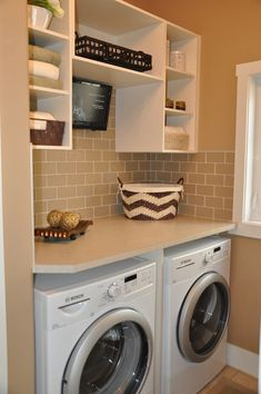 Sarasota Homes - laundry/mud rooms - chevron basket, upper cabinets, laundry room cabinets, open cabinets, beige subway tiles, white washer and dryer, front load washer and dryer,