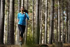 14342231 - woman running in wooded forest area, training and exercising for trail run marathon endurance  fitness healthy lifestyle concept