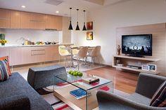 studio à aire ouverte - cuisine en bois clair, canapé gris foncé, table basse en bois et verre et meuble TV en bois