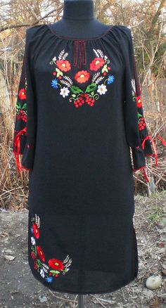 Hand embroidered Ukrainian dress with bright flowers on black cloth.