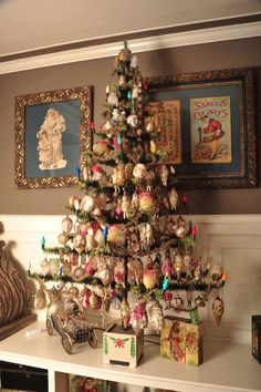 A feather tree with antique glass tree ornaments and a Christmas wood puzzle beneath the tree.
