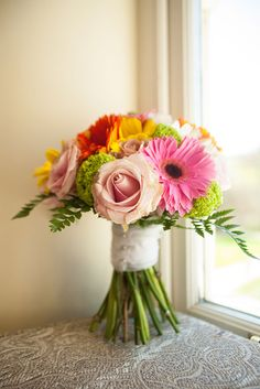 A brightly coloured wedding bouquet of pink, yellow and orange gerberas with pale pink roses #weddingbouquet #weddingphotography #bride