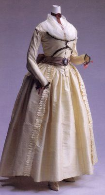 I LOVE this.  1790s Robe a L'Anglaise. Cream silk taffetta, with a zone/turque-like front and button closure. Black lace decorates the front of the bodice and the cuffs, the latter lacing with wine-colored ribbons. The sash sports a metal buckle with a painted porcelain center, on a striped silk sash.