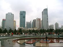 The People's Square is a large public square in the Huangpu District of Shanghai, China. It is south of Nanjing Road (West) and north of Huaihai Road (East). People's Square is the site of Shanghai's municipal government headquarters building, and is used as the standard reference point for measurement of distance in the Shanghai municipality.