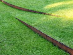 Lawn with corten steel edging. Maybe a good way to deal with different levels between patio and raised beds, but you can still mow and negotiate with a wheelbarrow.