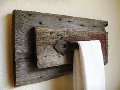 Rusty old cabinet pull or gate handle mounted on salvaged lumber for a hanging rack for a small towel.