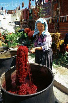 A woman dyes wool for carpet weaving in Goreme, Turkey.