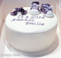 Christening cake with violet baby shoes.
