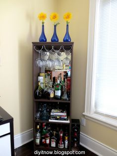 Under the stairs? Prop up leaf on top for drink mixing surface? Dowel or decorative railing on the front to hold bottles in place.