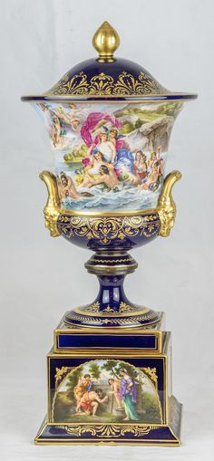 A Very Fine Pair of Vienna Cobalt Blue Porcelain with Finely Painted Allegorical Figures Covered Urns with Male Mask Handles. Each covered urns and covers; cobalt blue ground; loop handles terminating at classical male mask heads; allegorical figures titled under the base of one Romulus and Remus and Galathea, the other with Diana and Bade and Telemachus and Calypso.